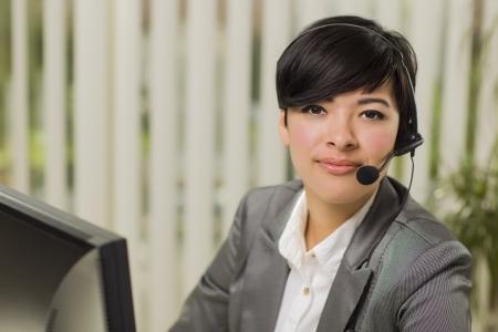Aantrekkelijke jonge gemengd ras vrouw glimlacht dragen headset Dichtbij Computer Monitor. Stockfoto