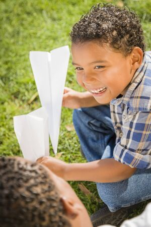 diversity children: Happy Mixed Race Father and Son Playing with Paper Airplanes in the Park.