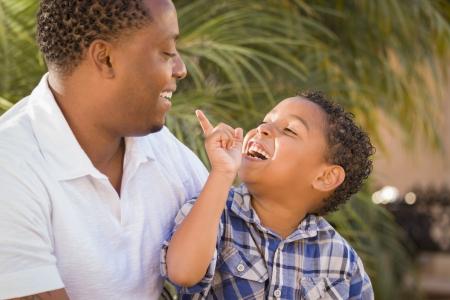hispanic boy: Padre feliz descendencia mixta e hijo jugando en el parque. Foto de archivo