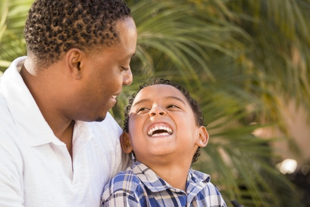 Happy Mixed Race Father and Son Playing in the Park. photo