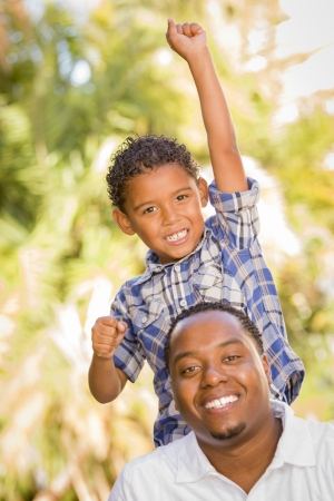 Happy Mixed Race Father and Son Cheering with Fist in the Air at the Park. photo
