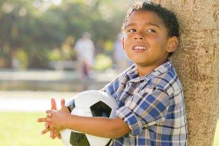 niños tristes: Boy carrera mixta de cartera balones de fútbol en el Parque contra un árbol.