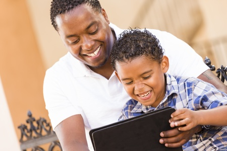 modern parents: Happy African American Father and Mixed Race Son Having Fun Using Touch Pad Computer Tablet Outside.