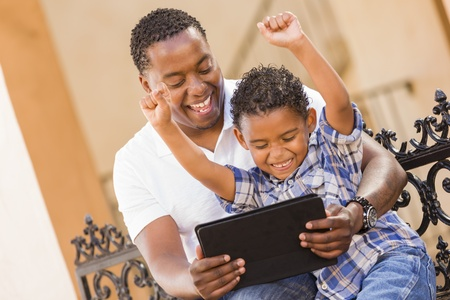 latino man: Happy African American Father and Mixed Race Son Having Fun Using Touch Pad Computer Tablet Outside.