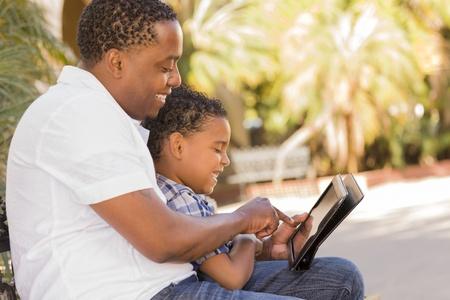 mixed race: Padre Feliz americano africano y del Hijo raza mezclada que se divierten Con Touch Pad Tablet PC fuera. Foto de archivo