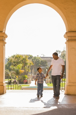 Happy African American Father and Mixed Race Son Holding Hands Walking in the Park. photo
