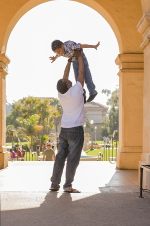 kinship: Happy African American Father Lifts Mixed Race Son Over His Head in the Park.