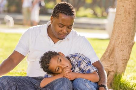 bambini tristi: African padre americano preoccupato per il suo Figlio, di sangue misto, seduti nel parco. Archivio Fotografico