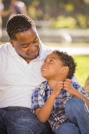 Happy African American Father and Mixed Race Son Playing in the Park. photo