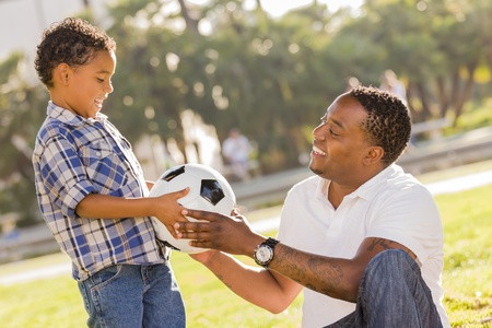 African American Father Hands New Soccer Ball to Mixed Race Son at the Park. Banco de Imagens