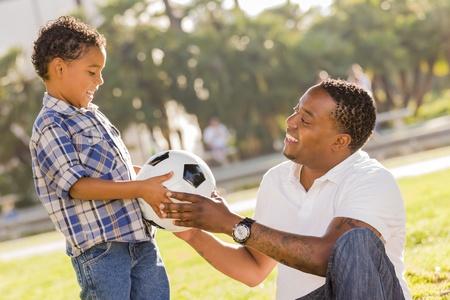 padres e hijos felices: Africanos Manos padre estadounidense de Nueva pelota de fútbol de Son descendencia mixta en el Parque.