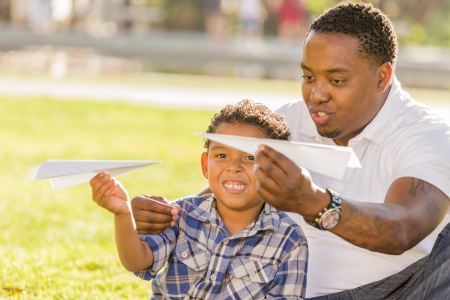 african american male: Happy African American Father and Mixed Race Son Playing with Paper Airplanes in the Park.