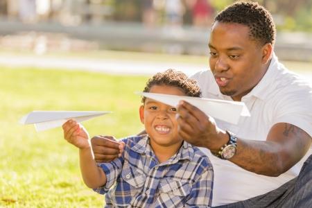 mixed race: Padre feliz de �frica y de Am�rica Hijo descendencia mixta Jugar con aviones de papel en el Parque. Foto de archivo