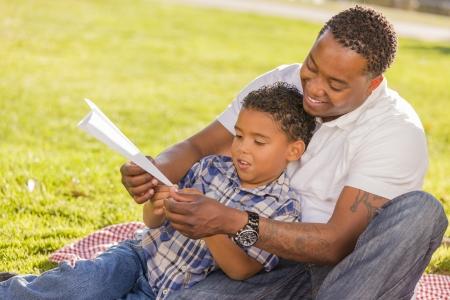kinship: Happy African American Father and Mixed Race Son Playing with Paper Airplanes in the Park.