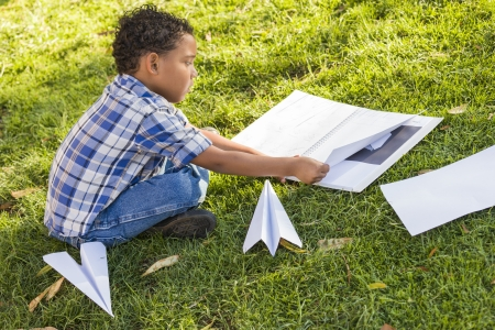 Mixed Race Boy Learning How to Fold Paper Airplanes Outdoors on the Grass. photo