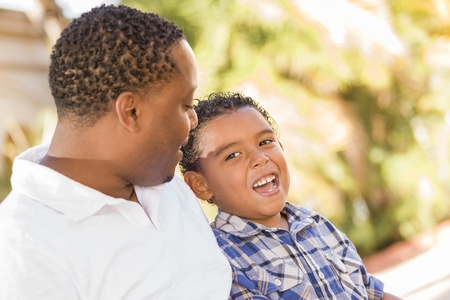 single parents: Happy African American Father and Mixed Race Son Talking in the Park.