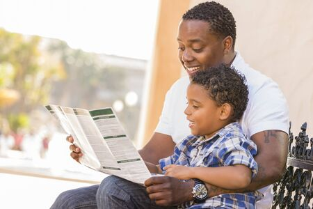 pamphlet: Happy African American Father and Mixed Race Son Having Fun Reading Park Brochure Outside.