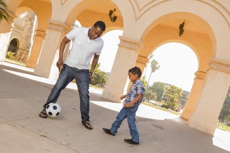 Mixed Race Father and Son Playing Soccer Outside in the Courtyard. photo