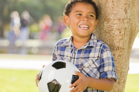 child sad: Mixed Race Boy Holding Soccer Ball in the Park Against a Tree.