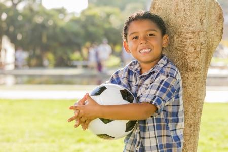 niños latinos: Boy carrera mixta de cartera balones de fútbol en el Parque contra un árbol.