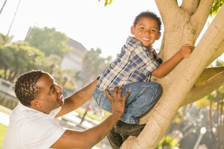 ni�o empujando: Padre feliz descendencia mixta Ayudar Hijo trepar a un �rbol en el Parque. Foto de archivo