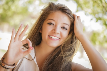 french model: Attractive Smiling Mixed Race Girl Portrait with Okay Hand Sign Outdoors. Stock Photo