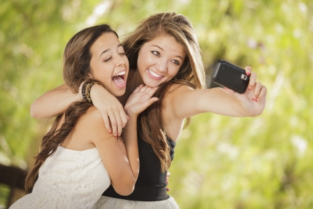 self portrait: Two Attractive Mixed Race Girlfriends Taking Self Portrait with Their Phone Camera Outdoors.