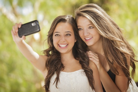 야외에서 자신의 휴대 전화 카메라로 자기 초상화를 복용 두 매력적인 혼합 된 인종의 여자 친구.