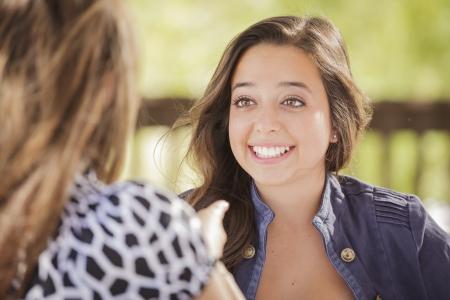 dos personas hablando: Novias Atractivas risa sentada al aire libre.