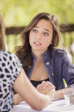 Muchacha atractiva de consolar a un amigo sentado al aire libre. Foto de archivo