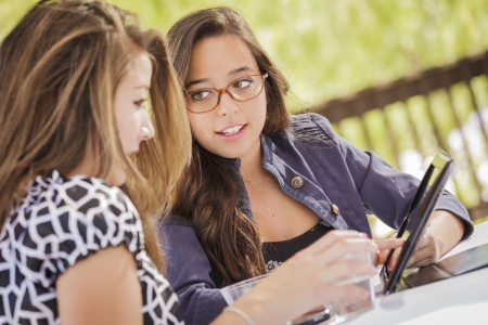 students studying: Attractive Mixed Race Girls Smiling and Talking While Working on Tablet Computer Sitting Outdoors.