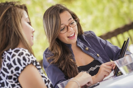 Attractive Mixed Race Girls Smiling and Talking While Working on Tablet Computer Sitting Outdoors. photo