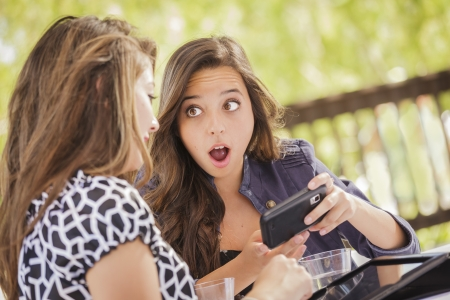 Attractive Shocked Mixed Race Girls Working on Smart Mobile Phone and Tablet Computer. photo
