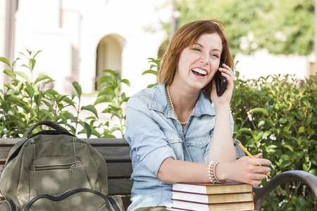 Smiling Young Pretty Female Student Outside on Cell Phone with Backpack and Books Sitting on Bench. photo
