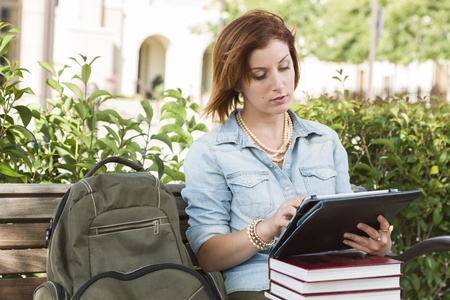 school campus: Young Pretty Female Student Outside with Backpack and Books Sitting on Bench Using Touch Tablet.