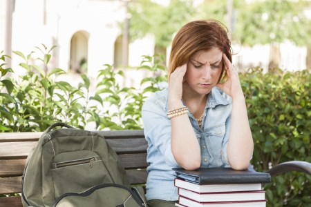 Young Female Student with Headache Sitting with Books and Backpack on Campus Bench. photo