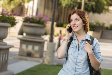 Smiling Young Pretty Female Student with Backpack Walking Outside Using Cell Phone. photo