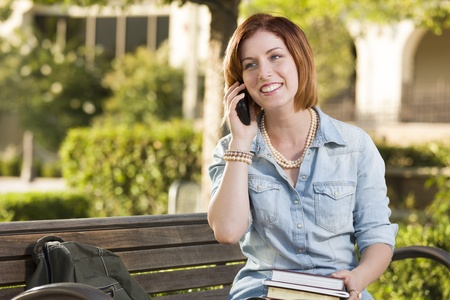 girl sit: Smiling Young Pretty Female Student Outside on Cell Phone with Backpack and Books Sitting on Bench. Stock Photo
