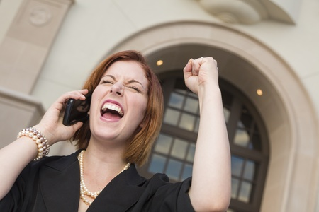 Young Businesswoman with Fist in the Air On Cell Phone in Front of Building. photo