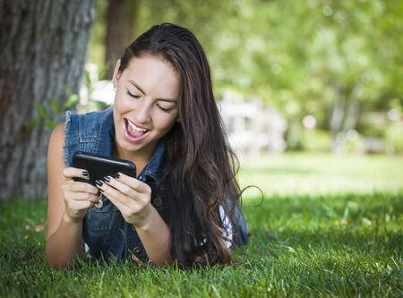 Attractive Happy Mixed Race Young Female Texting on Her Cell Phone Outside Laying in the Grass. photo