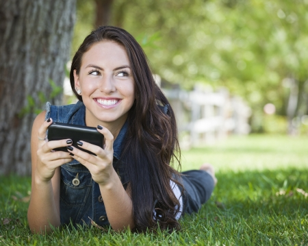 phone: Attractive Happy Mixed Race Young Female Texting on Her Cell Phone Outside Laying in the Grass.