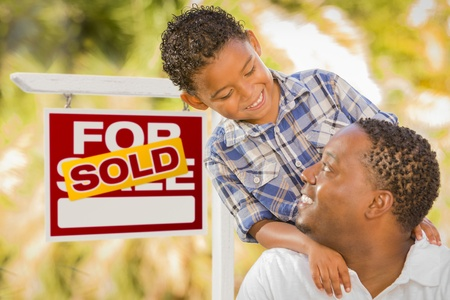 Happy African American Father and Mixed Race Son in Front of Sold Real Estate Sign. photo