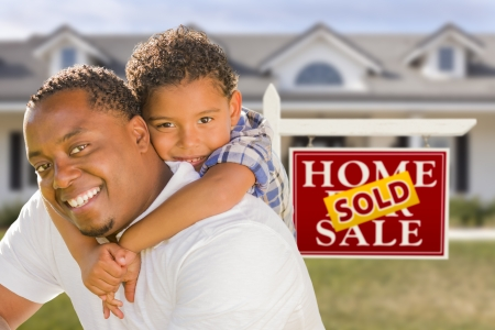 Happy Mixed Race Father and Son In Front of Sold Real Estate Sign and New House. Stock Photo