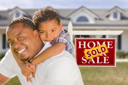 nieruchomosci: Szczęśliwa Mixed Race Ojciec i syn przed Sprzedane prawdziwy znak nieruchomości i nowy dom. Zdjęcie Seryjne
