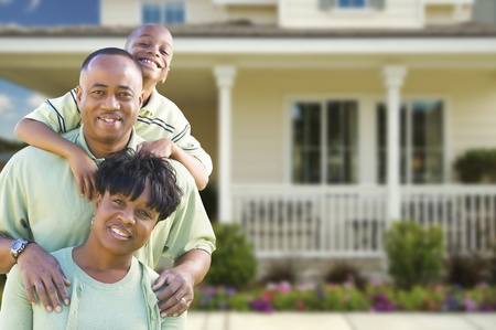 home front: Happy Attractive African American Family in Front of Beautiful House.