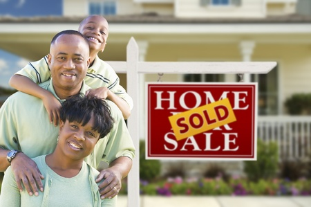 Happy African American Family In Front of Sold Real Estate Sign and House. photo