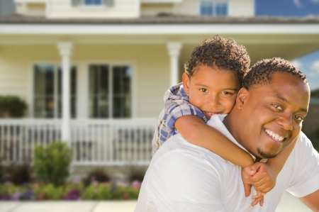 home front: Happy Playful African American Father and Mixed Race Son In Front of House.