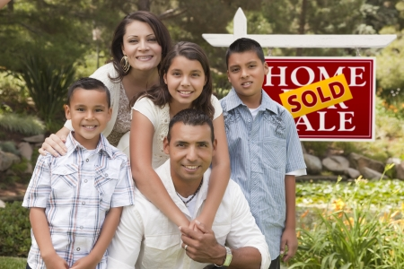 Happy Hispanic Family in Front of Sold Home for Sale Real Estate Sign. Stock Photo