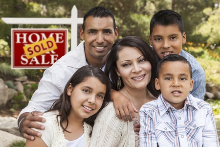 Happy Hispanic Family in Front of Sold Home for Sale Real Estate Sign. Banque d'images