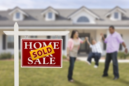 Sold Real Estate Sign and Playful Hispanic Family in Front of House. Stock Photo
